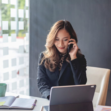 Happy young asian woman talking on the mobile phone and smiling while sitting at her working place in office.